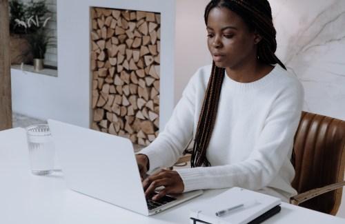 Woman writing on a laptop